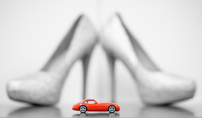 21334a95e36 Red toy car against the blurred backdrop of silver glamour high heeled shoes