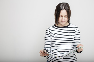 Young attractive woman carefully reading a magazine in their hands on a blank gray wall background in a striped sweater