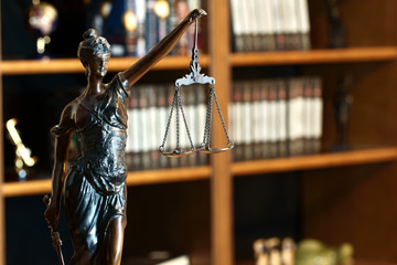 Goddess of justice statue in lawyer cabinet on bookshelf background