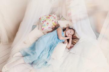 Little girl in a blue dress smiles in a dream