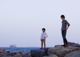 Father and son standing at seaside