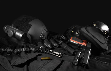 Black military ammunition tactical gun, helmet, gloves, cartridge belt, bandolier, gun shell, knife, binocular and knee protection laying on a black table.