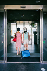 Back shot of two women entering the hotel