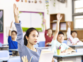 asian pupil raising hands in classroom