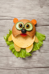 Panda created from bread, cheese and vegetables on wooden background