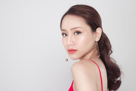 Beautiful stylish asian woman wearing red dress on grey background.