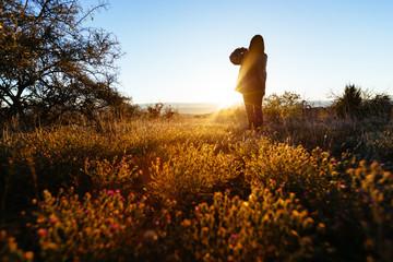Woman Taking Photo of Sunrise