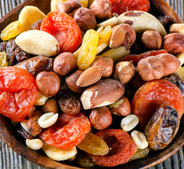 Mix nuts and dried fruits on a rustic wooden background.