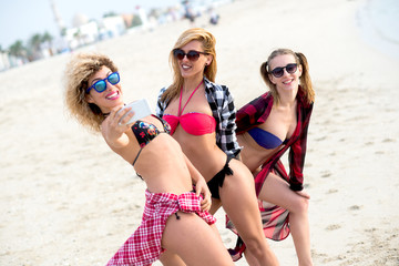 Three young best friends taking selfies at beautiful beach.
