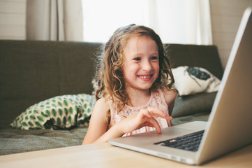 happy child using laptop at home. School girl learning with computer and internet indoor.