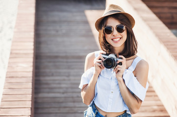 Young beautiful tourist woman taking photographs with retro styled digital photo camera