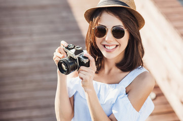 Young beautiful tourist woman taking photographs with digital retro styled photo camera