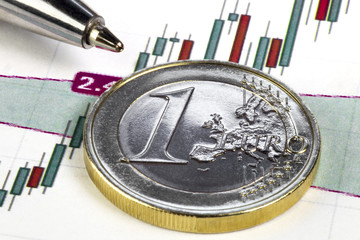 Concept of stock market currency trading. Chart with stock market prices. One euro coin lying on the diagram. Ball pen pointing on the one euro coin. Macro image.
