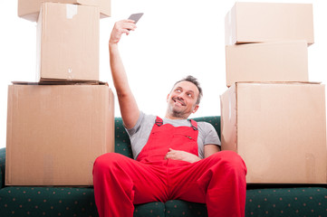 Mover man sitting on couch talking a selfie with smartphone
