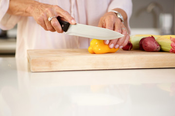 older woman cutting fresh vegetables in kitchen