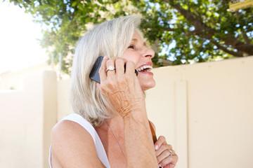 beautiful older woman talking on mobile phone outside