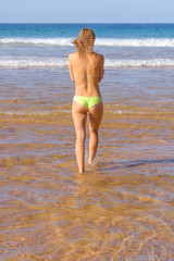 topless young woman walking in seashore