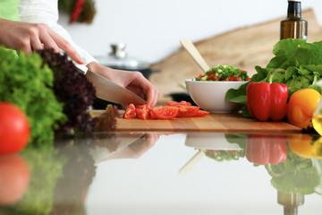 Closeup of human female hands cooking vegetables salad in kitchen on the glass table with reflection. Healthy meal and vegetarian concept