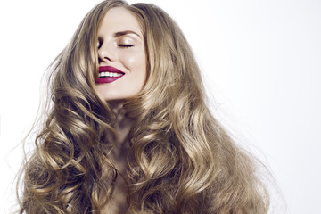girl with closed eyes red lips and healthy hair on the face smiling