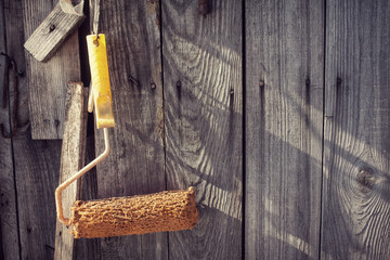 Yellow paint roller hanging on old wooden background