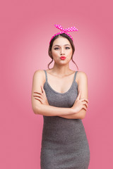 Beautiful asian girl with pretty smile in pinup style on pink background