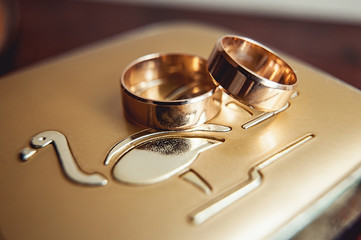 wedding rings on a gold metal surface