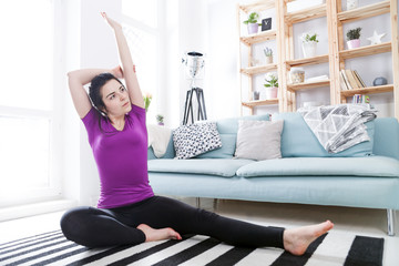 Young woman exercising on carpet at home interior
