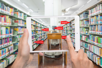 computer in a libAugmented reality education concept. Hand holding digital tablet smart phone use AR application to check library category