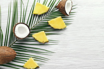 Composition of fresh pineapple slices and coconuts on light wooden background