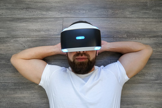 Adult Man lying on his back in virtual glasses on a wooden floor, hands behind his head