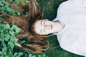 Beautiful pale faced redhead woman lying on the fresh green grass wearing a white vintage shirt, top view