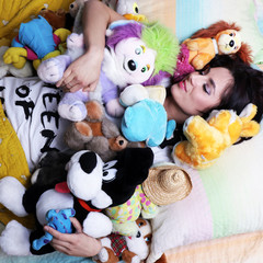 Woman sleeping good with her soft toys like a child in her bed
