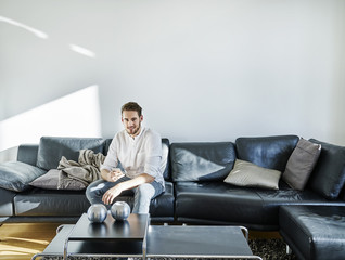 Smiling man sitting on couch holding cell phone