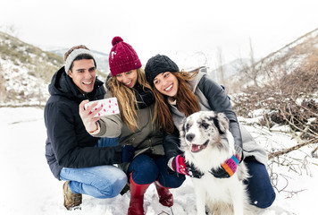 Three friends having fun taking a selfie with a dog in the snow