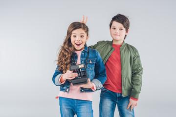 Children having fun with retro camera on gray