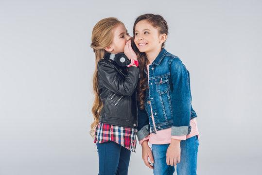 Two smiling little girls whispering secrets on grey