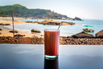 Strawberry cocktail with a straw in a glass stands on the table on background of sea.