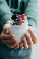 Vertical photo Boy hands with Pudding with chia seeds, yogurt and fresh fruits: Strawberries, blueberries and blackberries in glass jars on wooden background