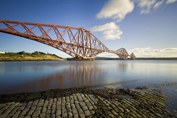 The Forth Rail Bridge is a cantilever railway bridge opened in 1890 that crosses the Firth of Forth between Edinburgh and Fife in Scotland. It is the second largest bridge of its kind in the world.