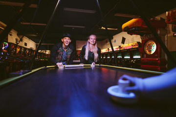 Smiling young friends playing air hockey game