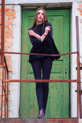 Stylish girl posing against abandoned house and old green door.