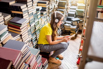 Young woman student listening to the music sitting on the heap of books at the old library