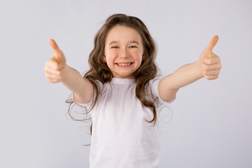 Little girl showing thumbs up gesture in a white T-shirt isolated on white background.