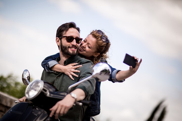 Young couple on motorbike taking a selfie