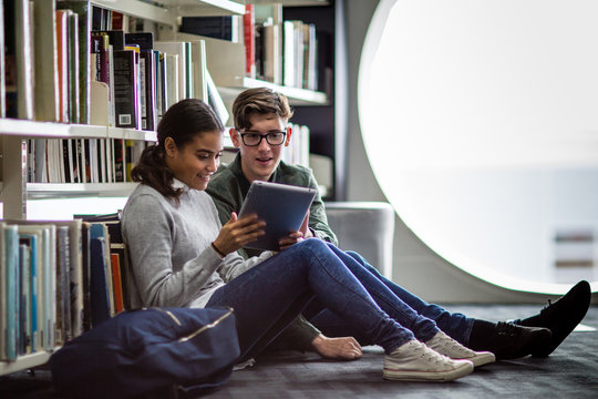 Students reading digital tablet in library