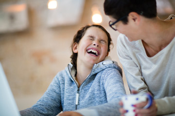 Daughter laughing with Mother at home