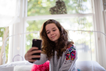 Teenager in bedroom taking a selfie