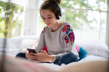 Teenager in bedroom listening to music on smartphone