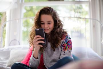 Teenager in bedroom looking at smartphone