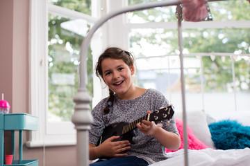 Girl playing a ukulele looking at camera